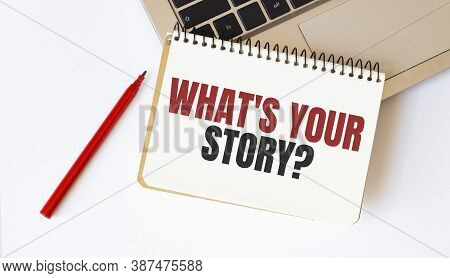 Laptop, Red Pen And Notepad With Text What Is Your Story In The White Background