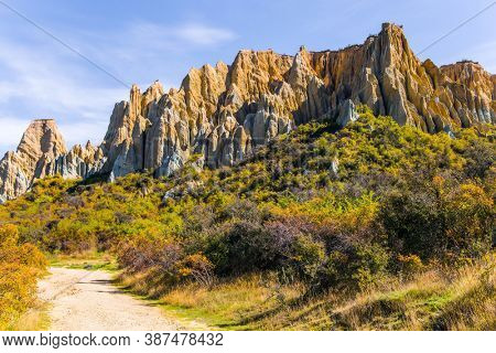 Ridges of the Clay Cliffs separated by narrow ravines. Dirt path passes around majestic clay cliffs. New Zealand, South Island. The concept of exotic, extreme, natural and photo tourism
