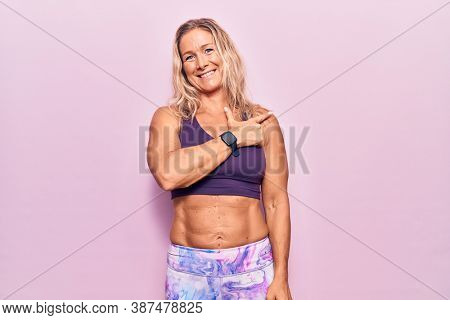 Middle age caucasian blonde woman wearing sportswear over pink background cheerful with a smile of face pointing with hand and finger up to the side with happy and natural expression on face