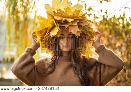 Young Woman With A Wreath Of Yellow Autumn Leaves. Outdoors Portrait. Autumn.