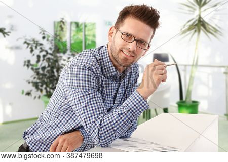 Young entrepreneur looking up from business report in small business office.