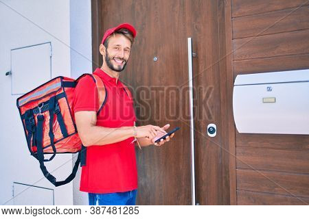Caucasian delivery man wearing red uniform and delivery backpack smilly happy outdoors using smartphone