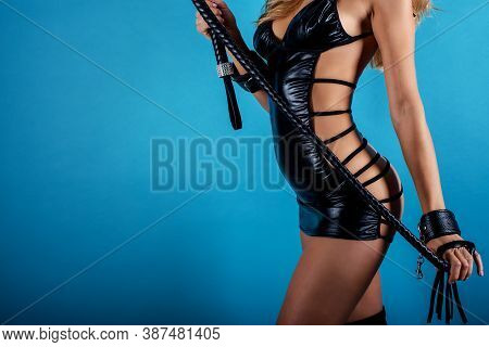 Woman In Bdsm Style With Whip And Lingerie. Blue Background