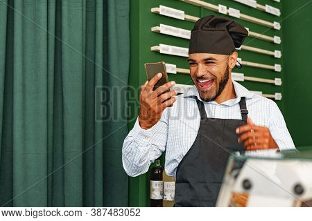 African American Man Barista Using His Smartphone And Laughing While Standing At The Counter Of Coff