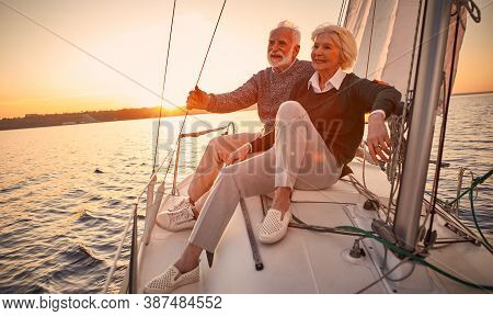 Beautiful And Happy Senior Couple In Love Sitting On The Side Of Sailboat Or Yacht Deck Floating In