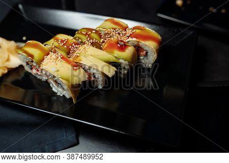 Golden Dragon Sushi Roll With Tuna, Eel, Cucumber, Sesame Seeds And Tobiko Caviar.