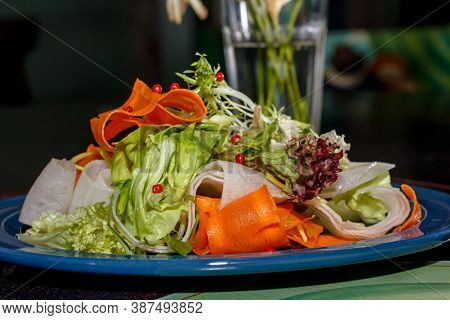 Vegan  Salad Of Fresh Vegetables: Lettuce, Carrots And Daikon Is On The Plate