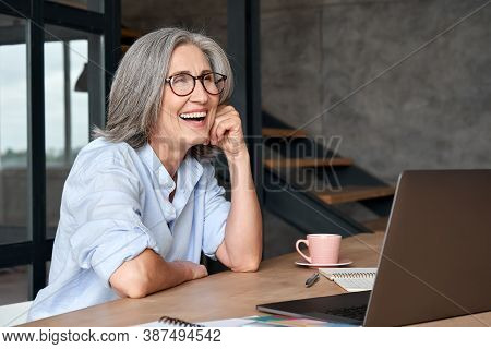 Happy Stylish Mature Middle Aged Business Woman Wearing Glasses Laughing Sitting At Workplace Desk W