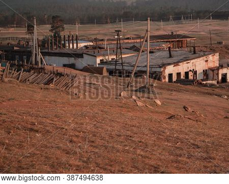 Ruins Of Old Destroyed White Factory Building In Field, Steppe With Dry Yellow, Red Grass, Electric