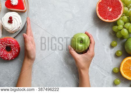 Concept Of Choice. Top View Of Woman Holding Apple At Grey Table, Closeup