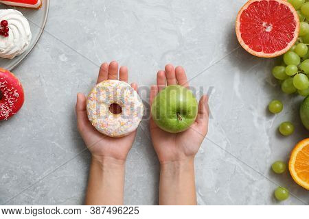 Concept Of Choice. Top View Of Woman Holding Apple And Doughnut At Grey Table, Closeup