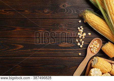 Tasty Sweet Corn Cobs On Wooden Table, Flat Lay. Space For Text