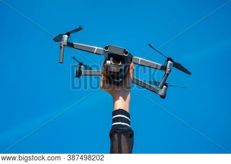 Woman Holding Drone Or Quadcopter Isolated On The Blue Sky Background. Flying Drone Outside In Summe