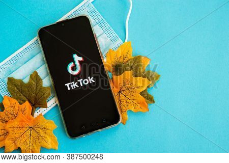 Tver, Russia - September 25, 2020, Medical Mask And Tik Tok Logo On The Smartphone Screen On Blue Ba