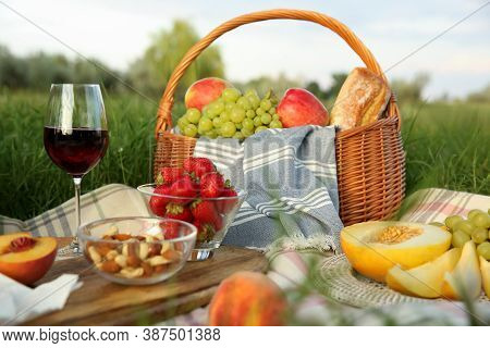 Picnic Blanket With Delicious Food And Wine On Green Grass