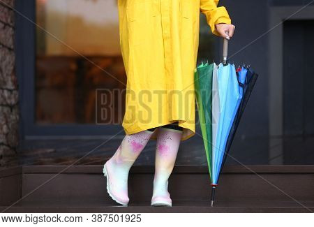 Woman Wearing Raincoat And Rubber Boots Holding Umbrella Outdoors, Closeup
