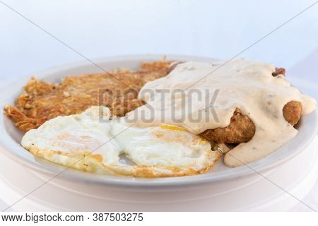 Generous Serving Meal Of A Hearty Chicken Fried Steak, Eggs, And Hash Browns Dripping With Country G