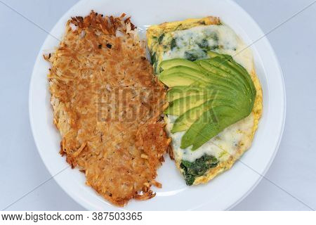Overhead View Of Generous Serving Meal Of A Hearty Avocado Omelette Covered With Gravy Combined With