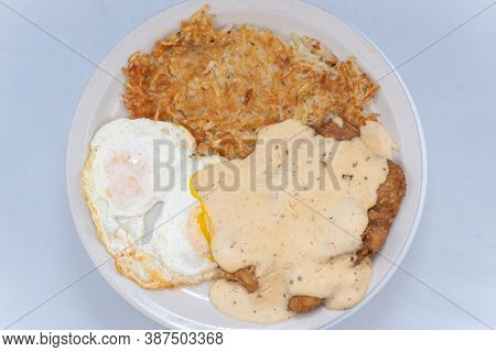 Overhead View Of Generous Serving Meal Of A Hearty Chicken Fried Steak, Eggs, And Hash Browns Drippi