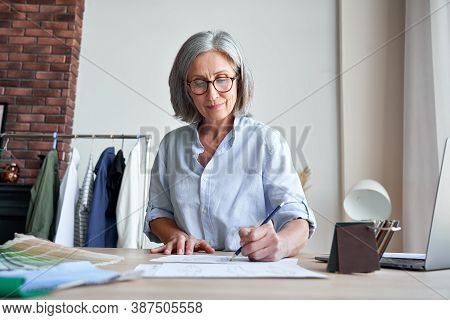 Smiling Middle Aged Stylish Woman Fashion Designer Drawing Sketches In Studio. Mature Old Adult Eleg