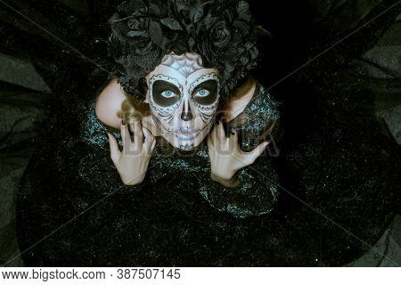 Scary and beautiful Calavera Catrina looking up at camera over dark background. Fashion model with sugar skull makeup. Dia de los muertos. Day of The Dead. Halloween.