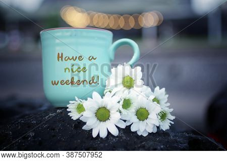 Weekend Greeting With Text Message Written On A Cup Of Tea Or Coffee With White Daisy Flowers On Sea