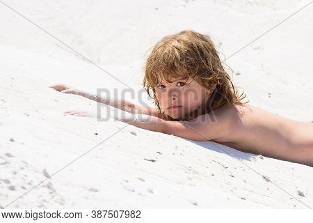Child Boy Play With Sand In The Sea. Kid Sun Protection, Tan, Suntan. Gentle Kids Skin Tanning