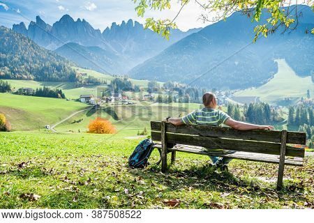 Man Sitting On Bench And Looking At The Picturesque Village Of Santa Magdalena In Italy On The Slope