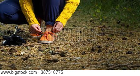 Sporty Hiking Woman Tying Shoelaces On Her Jogging Shoes While Taking A Break After Hiking In Autumn