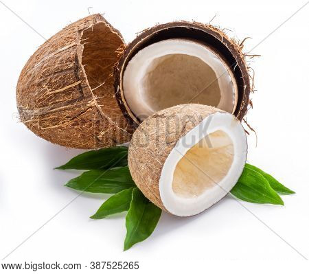 Split coconut fruit over green leaves isolated on white background.
