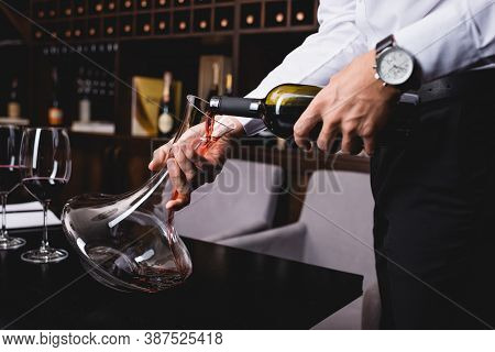 Cropped Of Sommelier In Shirt Pouring Wine From Bottle In Decanter