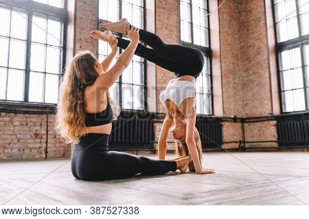 Two Young Females Do Complex Of Stretching Yoga Asanas In Loft Style Class. Training, Handstand
