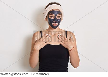 Adorable Female With Hairband Looking At Camera, Posing In Sleeveless T Shirt, Doing Beauty Procedur