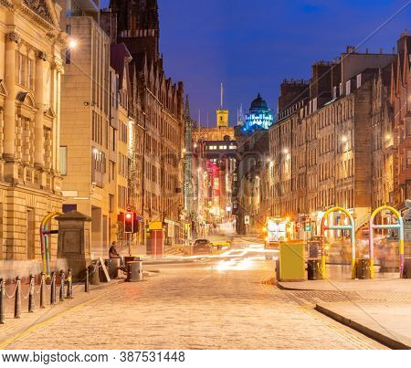 Cityscape of Royal Mile street Edinburgh old town at sunset dusk, Edinburgh, Scotland United Kingdom. UK Scotland landmark consumerism and tourism concept.