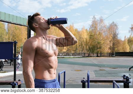 Toned Muscular Man Drinking Whey Protein Cocktail After Workout. Autumn Stadium, Outdoors Aclive Tra