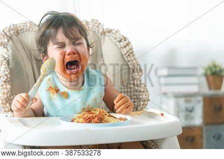 Lovely Baby Girl Crying While Eating Spaghetti And Making A Mess. Family Leave Baby Alone, Eating Pa