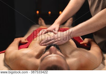 A Male Massage Therapist Makes A Massage Of The Pectoral Muscles And Chest. Sports Massage For A Mus