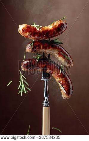 Grilled Bavarian Sausages With Rosemary.  Sausages  On A Fork Sprinkled With Rosemary. Brown Backgro