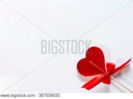 One Sweet Red Lollipop Heart With A Bow For Valentines Day Over Light Background With Copy Space. Lo