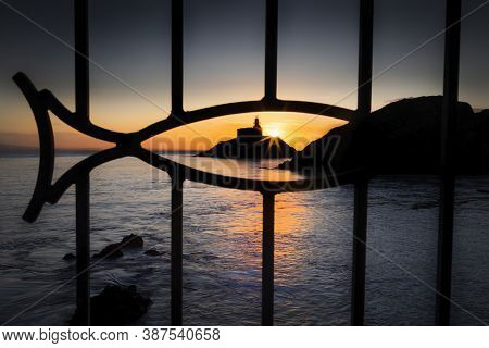 Dawn At Mumbles Lighthouse Framed Through A Fish In The Safety Railings, Swansea, South Wales Uk