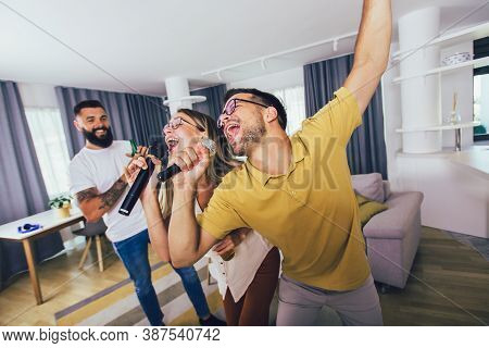 Group Of  Friends Having Fun At Home. They Are Drinking Beer And Having Karaoke.