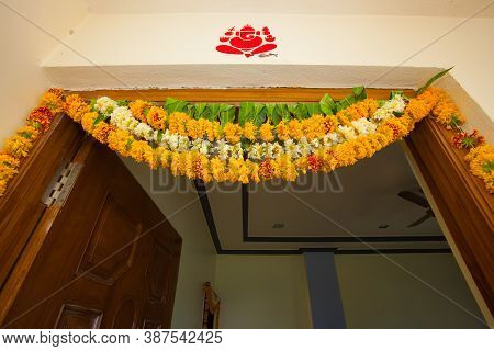 Indian Typical House Door Closeup With Door Hanging Flowers & Auspicious Drawing Of Lord Ganesha.