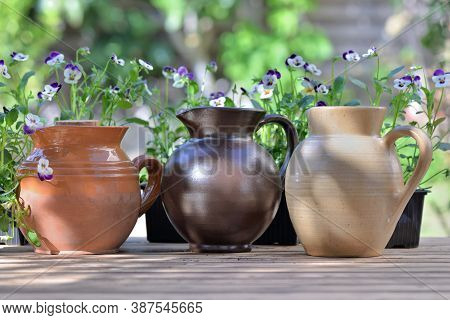 Three Water Jugs Placed On A Table In Front Of Viola Flowers On A Table A  In Garden