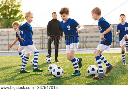 Happy Boys On A Sports Training Class With Young Coach. School Age Children Making Sport. Kids Kicki