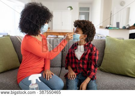 Mixed race mother with son enjoying family time together at home, social distancing and self isolation in quarantine lockdown, sitting on a couch, putting face masks on