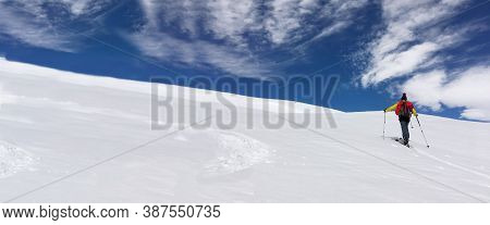 Man Ski Touring Climbing Snow-covered Mountain Under Blue And Cloudy Sky