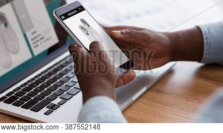 Black Man Shopping Online With Smartphone And Laptop Buying Shoes In Internet Sitting At Desk Indoor