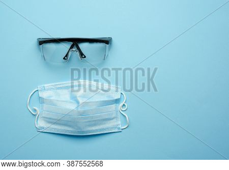 Transparent Plastic Protective Medical Glasses And Disposable Mask On A Blue Background, Top View, C