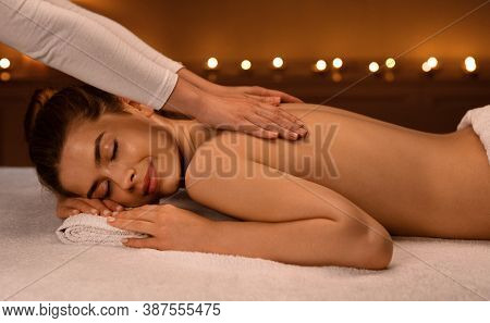Relaxed Young Woman Having Healing Body Massage At Newest Luxury Spa Decorated With Lightened Candle