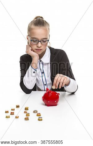 Portrait Of Teenage Girl In Dark Jacket Putting Coin Into The Piggybank For Savings. Vertical Image
